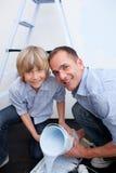 Père de sourire et son fils préparant la peinture Photos stock