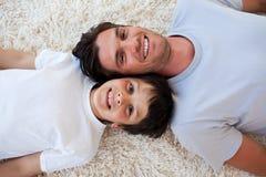 Père de sourire et son fils se trouvant sur l'étage Images stock