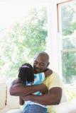 Père de sourire heureux à étreindre avec sa fille dans le divan Photos libres de droits