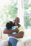 Père de sourire heureux à étreindre avec sa fille dans le divan Images stock