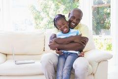 Père de sourire heureux à étreindre avec sa fille dans le divan photographie stock