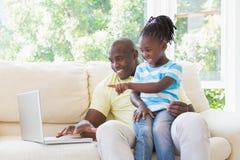 Père de sourire heureux à l'aide de l'ordinateur portable avec sa fille sur le divan Images stock