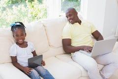 Père de sourire heureux à l'aide de l'ordinateur portable et sa fille à l'aide du comprimé sur le divan Photo stock