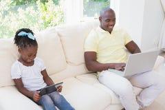 Père de sourire heureux à l'aide de l'ordinateur portable et sa fille à l'aide du comprimé sur le divan images stock