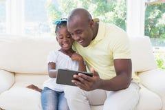 Père de sourire heureux à l'aide du comprimé numérique avec sa fille sur le divan photographie stock libre de droits