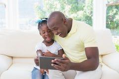 Père de sourire heureux à l'aide du comprimé numérique avec sa fille sur le divan photographie stock