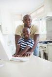 Père de sourire heureux avec son fils à l'aide de l'ordinateur Photo stock