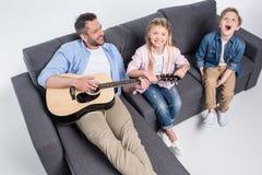 Père de sourire jouant la guitare et les enfants heureux mignons s'asseyant sur le sofa image libre de droits