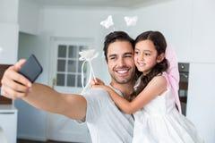 Père de sourire prenant l'autoportrait avec la fille dans le costume féerique Photo stock