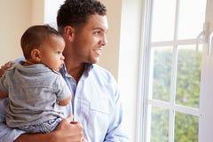 Père de sourire Standing By Window avec le fils de bébé à la maison Photos libres de droits