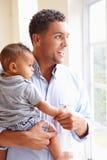 Père de sourire Standing By Window avec le fils de bébé à la maison Images stock