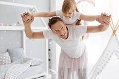 Père drôle charismatique jouant avec sa fille Image stock