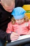 Père enseignant le petit descendant à écrire Photos libres de droits