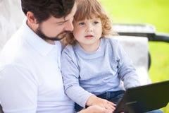 Père enseignant sa fille à l'aide de l'ordinateur portable Image stock