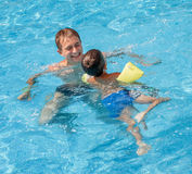 Père enseignant son fils à nager Photographie stock libre de droits