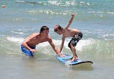Père enseignant son jeune fils à surfer Image stock