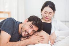 Père entendant son fils ou fille donnant un coup de pied le contrôle sain à l'intérieur du ventre de mère en se reposant sur se t photos libres de droits