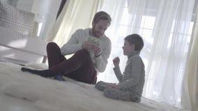 Père espiègle de barbe s'asseyant avec son fils au tapis et tenant l'argent Le papa et l'enfant ont mis un doigt au nez joyeux banque de vidéos