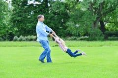 Père espiègle et fille ayant l'amusement dans le jardin Photo libre de droits
