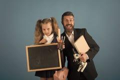 Père et écolière avec les visages heureux et grincheux sur le bleu photos stock