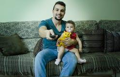 Père et bébé regardant la TV Image stock