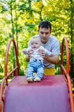 Père et bébé sur une glissière images stock