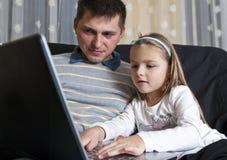 Père et daugter avec l'ordinateur portatif Image libre de droits