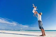 Père et descendant à la plage Photographie stock libre de droits