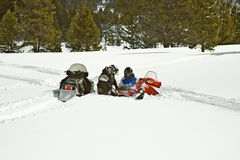 Père et descendant avec le Snowmobile coincé Image libre de droits