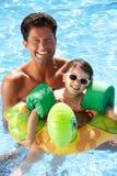 Père et descendant ayant l'amusement dans la piscine Image libre de droits