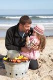 Père et descendant ayant le barbecue sur la plage Photos libres de droits