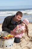 Père et descendant ayant le barbecue sur la plage Image stock