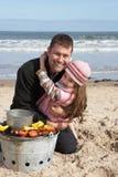 Père et descendant ayant le barbecue sur la plage Photos stock