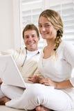 Père et descendant de l'adolescence sur le sofa blanc avec l'ordinateur portatif Image stock