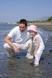 Père et descendant jouant en mer Images libres de droits