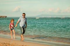 Père et descendant marchant sur la plage Photographie stock