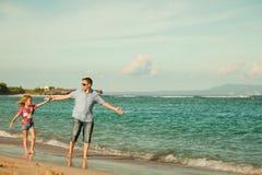 Père et descendant marchant sur la plage Photos libres de droits