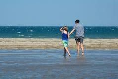 Père et descendant marchant sur la plage photographie stock libre de droits