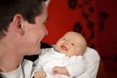 Père et descendant souriant à l'un l'autre Image stock