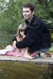 Père et descendant sur la passerelle au fleuve Photos stock