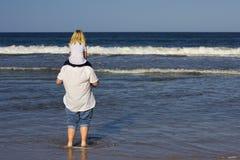 Père et descendant sur la plage Image libre de droits
