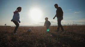 Père et deux enfants jouant dans le domaine avec du ballon de football Concept de sport banque de vidéos