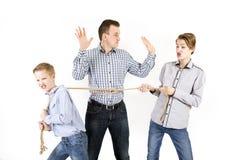 Père et deux fils reliés par la corde Photos stock