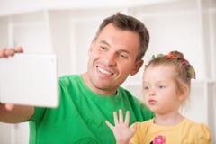 Père et enfant à l'aide du comprimé électronique à la maison Images stock