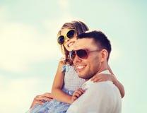 Père et enfant heureux dans des lunettes de soleil au-dessus de ciel bleu Image stock