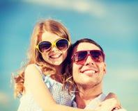 Père et enfant heureux dans des lunettes de soleil au-dessus de ciel bleu Images stock