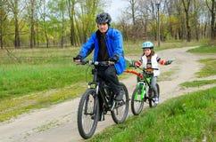Père et enfant heureux sur des vélos, recyclage de famille Images libres de droits