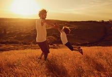 Père et enfant jouant en nature au coucher du soleil photographie stock libre de droits