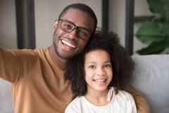 Père et enfant noirs de sourire prenant le selfie regardant la caméra photographie stock libre de droits