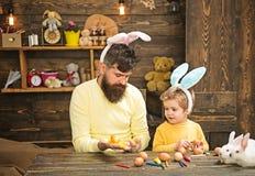 Père et enfant peignant des oeufs de pâques photographie stock libre de droits